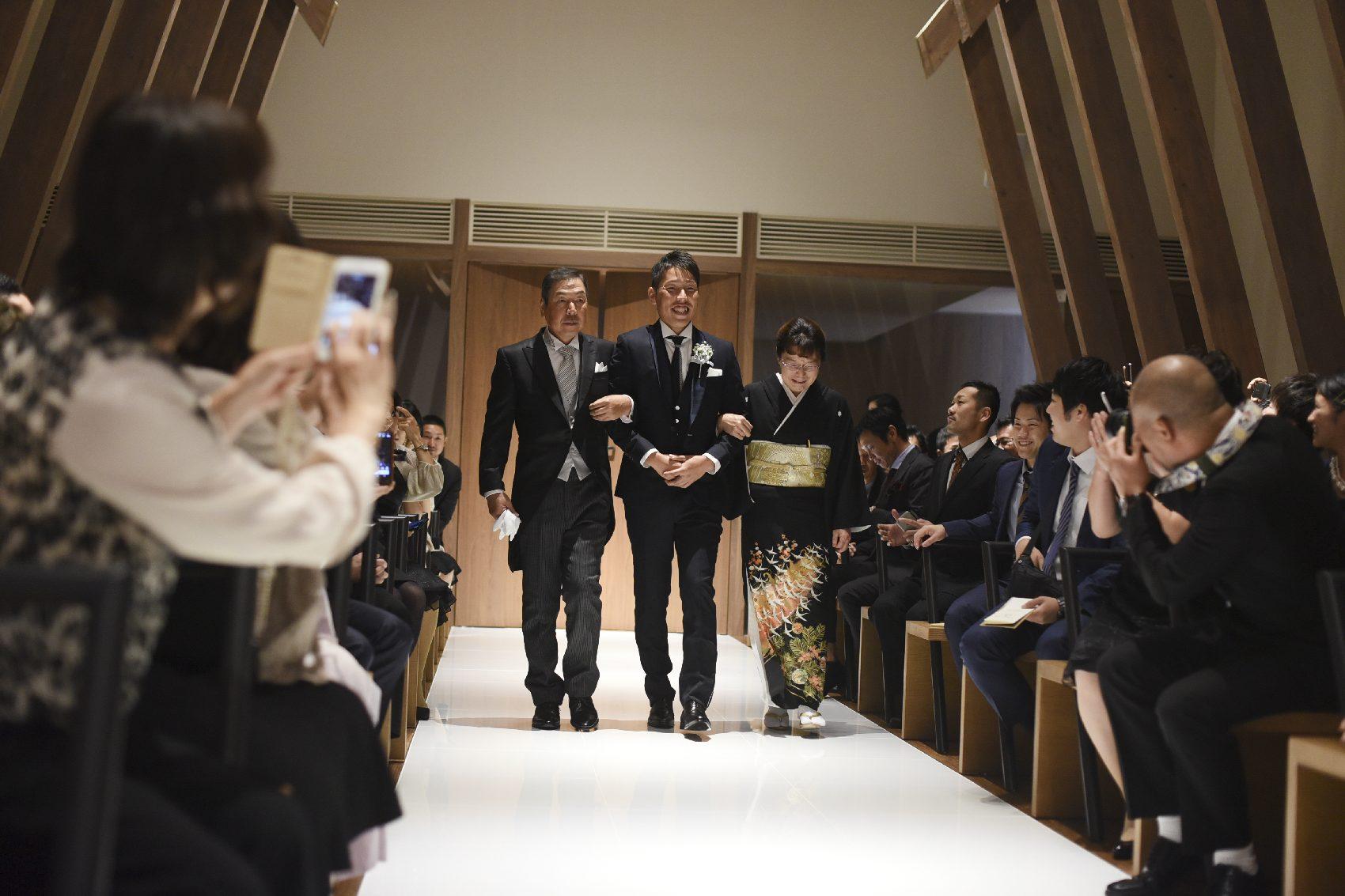 香川県高松市の結婚式場アナザースタイルのチャペルに新郎が両親と入場