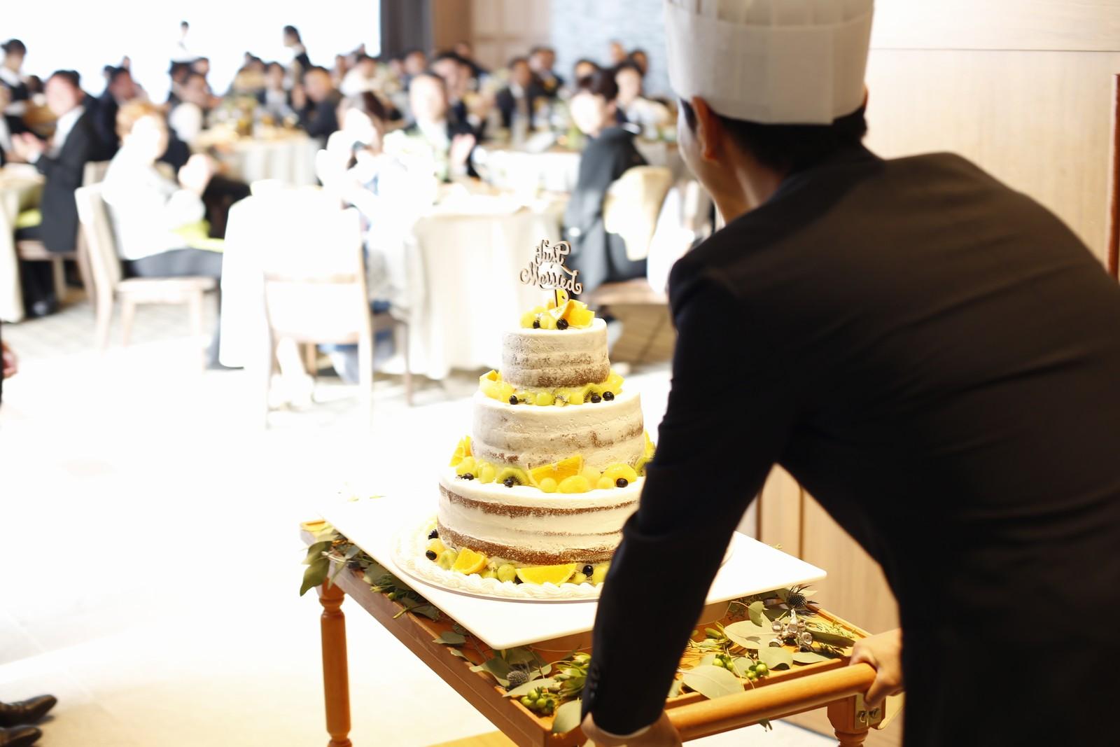 香川県高松市の結婚式場アナザースタイルのウエディングケーキを運ぶ友人ゲスト