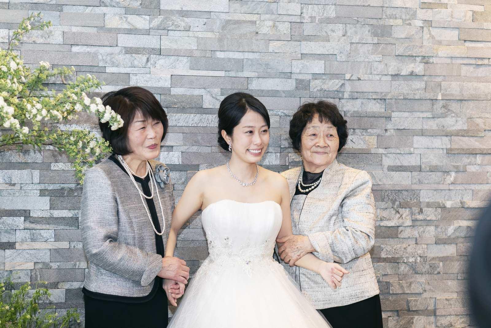 香川県高松市の結婚式場アナザースタイルのご親族様と記念撮影をする新婦